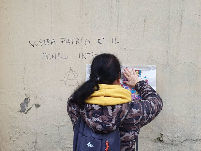 "Fig. 4: ""Our home is the whole wide world."" A participant in Ai Teng's intervention posts a nianhua print next to a graffiti with lyrics from the traditional anarchist song ""Stornelli d'Esilio"" (Pietro Gori, 1895)."