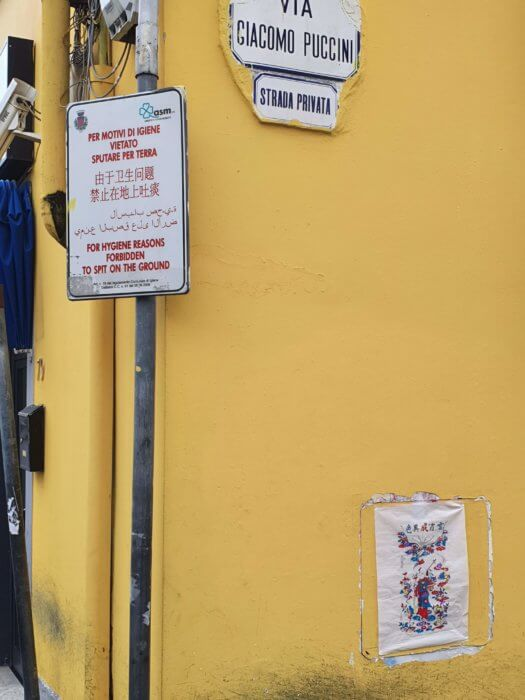 "Fig. 5: Nianhua prints next to one of the many multilingual ""cautionary"" street signs installed by the City Council."